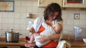 La mamma alimenta il suo bambino da una bottiglia, stante nella cucina vicino alla stufa Casalinga, congedo di maternità Alimenti archivi video