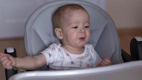 La mamma alimenta il suo bambino sveglio con un cucchiaio e comincia sorridere video d archivio