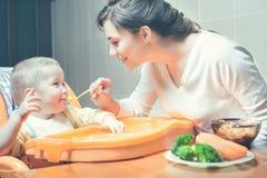 La mamma alimenta la minestra del bambino Alimenti per bambini sani e naturali Fotografia Stock