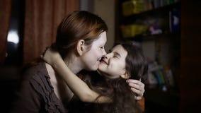 La mamma bacia la figlia che abbraccia la famiglia dell'interno di amicizia di amore della ragazza e della donna stock footage