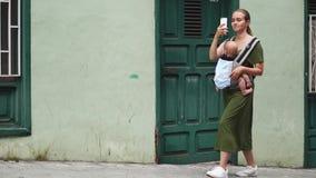 La mamma cammina giù una vecchia via stretta con un bambino in un'imbracatura e spara un video per le reti sociali circa il suo v archivi video