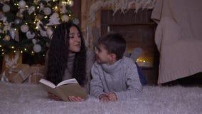 La mamma con capelli lunghi legge un libro a suo figlio e lo bacia che si trova sul pavimento vicino all'albero di Natale sul gio stock footage