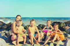 La mamma con i bambini sul mare sul mare sulla spiaggia, l'acqua si batte sulle pietre Foto d'annata tonificata fotografia stock libera da diritti