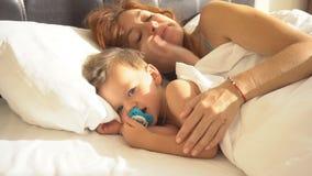 La mamma con il bambino del figlio ha svegliato di mattina sul letto stock footage