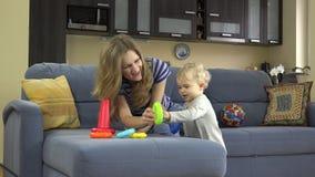 La mamma con la ragazza della figlia del bambino ha messo i cerchi del giocattolo sulle mani come i braccialetti video d archivio