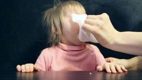 La mamma con un bambino gridante in sua mano con un fazzoletto pulisce il suo moccolo stock footage