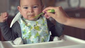 La mamma dà l'infante del bambino del bambino del cucchiaio nel bambino indipendente di svezzamento dei solidi della cucina del s stock footage