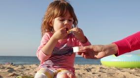 La mamma dà la patata fritta e la salsa della ragazza ragazza che si siede sulla sabbia sulla spiaggia contro il mare video d archivio