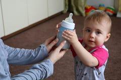 La mamma dà una bottiglia di latte al loro bambino piccolo fotografie stock