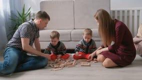 La mamma della famiglia, il papà e due fratelli gemelli giocano insieme la costruzione dai blocchi di legno sul pavimento video d archivio