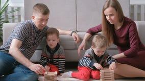 La mamma della famiglia, il papà e due fratelli gemelli giocano insieme la costruzione dai blocchi di legno sul pavimento stock footage