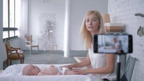 La mamma di blogger insegna a come cambiare la ragazza neonata del pannolino mentre registra la registrazione a scopo formativo s video d archivio