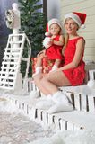 La mamma e la figlia nei vestiti del ` s di Santa stanno sedendo sotto la neve Fotografia Stock