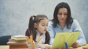 La mamma e la figlia si siedono alla tavola e leggono un libro Durante questo fondo grigio archivi video