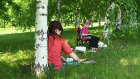 La mamma e la figlia sono impegnate nella creatività nel parco nella tonalità sotto gli alberi stock footage