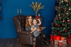 La mamma e la figlia stanno sedendo su una sedia di cuoio nella stanza del nuovo anno con un albero di Natale immagine stock