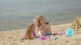 La mamma e la figlia sulla sponda del fiume mangiano il gelato Ricreazione esterna archivi video