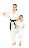 La mamma e la figlia con un sorriso in un kimono hanno colpito una mano su un fondo bianco Fotografie Stock Libere da Diritti