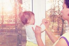 La mamma e la piccola neonata chiudono la finestra con una chiave Fotografia Stock