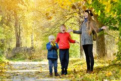 La mamma ed i suoi figli lanciano le foglie Parco di autunno Fotografie Stock Libere da Diritti