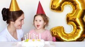 La mamma ed il bambino felici spegne le candele sulla torta di compleanno al partito Generi i suoi sorrisi, laughes ed applauso d stock footage