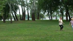 La mamma ed il figlio che giocano il recupero in parco, apprezzano insieme il tempo, infanzia felice video d archivio