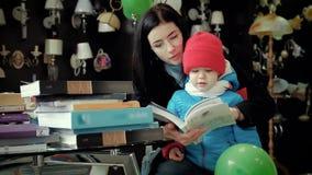 La mamma ed il figlio che lanciano attraverso il catalogo scelgono le merci nel deposito stock footage