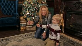 La mamma ed il figlio con le stelle filante si avvicinano all'albero di Natale stock footage