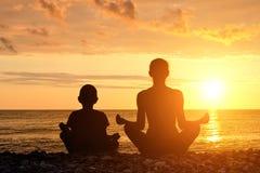 La mamma ed il figlio meditano su spiaggia nella posizione di loto Siluette, tramonto Immagine Stock