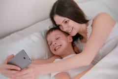 La mamma ed il figlio prendono il selfie sul suo telefono cellulare Mattina a letto Fotografia Stock