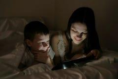 La mamma ed il figlio scelgono che cosa guardare prima di andare a letto sulla compressa sotto la coperta Fotografia Stock Libera da Diritti