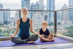 La mamma ed il figlio stanno praticando l'yoga sul balcone nei precedenti di grande città Mamma di sport con il bambino che fa il fotografia stock libera da diritti