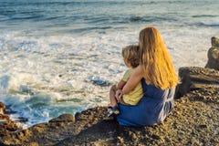 La mamma ed il figlio stanno sedendo su una roccia e stanno esaminando il mare Portra immagine stock libera da diritti