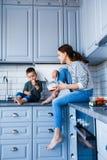La mamma ed il figlio stanno sedendo sulla tavola nella cucina fotografia stock libera da diritti
