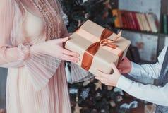 La mamma ed il figlio stanno tenendo un contenitore di regalo Colori caldi Concetto di Natale fotografia stock