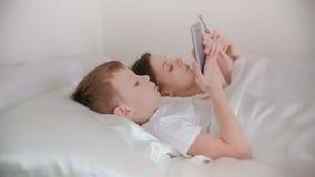 La mamma ed il figlio svegliano e Internet di lettura rapida in loro telefoni cellulari Vista laterale archivi video