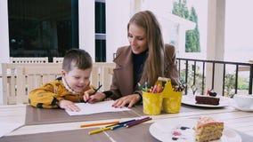 La mamma ed il giovane ragazzo disegnano con i pastelli alla tavola stock footage