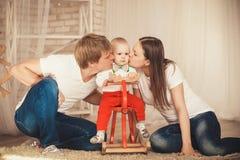 La mamma ed il papà baciano il loro piccolo figlio Immagini Stock