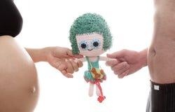 La mamma ed il papà preparano la bambola della ragazza per una nuova vita Fotografie Stock Libere da Diritti