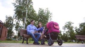 La mamma ed il papà riposano su un banco in parco con il passeggiatore di bambino stock footage
