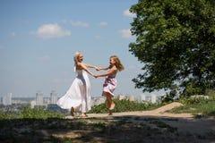 La mamma ed il piccolo dancing della figlia nella città parcheggiano Fotografie Stock Libere da Diritti