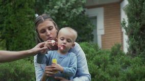 La mamma ed il ragazzino stanno iniziando le bolle di sapone nel cortile video d archivio