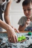 La mamma ed suo figlio cucinano i biscotti nella cucina domestica accogliente Un'immagine verticale fotografia stock libera da diritti