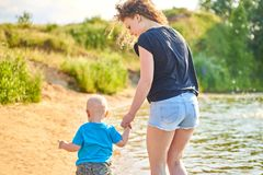 La mamma ed suo figlio stanno camminando lungo la sponda del fiume un giorno di estate caldo immagine stock