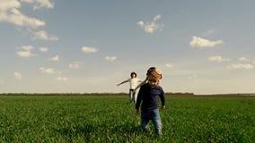 La mamma ed suo figlio stanno correndo lungo il prato inglese verde, mostrante il volo dell'aereo, in un movimento lento video d archivio