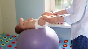 La mamma fa gli esercizi per lo sviluppo con il bambino sul fitball Concetto di sviluppo del bambino, mamma preoccupantesi, tonif stock footage