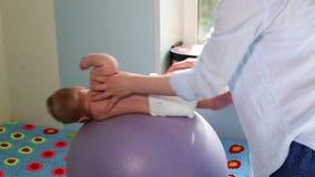La mamma fa gli esercizi per lo sviluppo con il bambino sul fitball Concetto di sviluppo del bambino, mamma preoccupantesi, tonif video d archivio