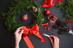 La mamma fa una corona di Natale con le sue proprie mani Immagine Stock