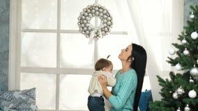 La mamma felice alza sul suo bambino che gioca prima dell'albero di Natale stock footage