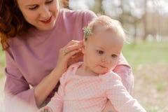 La mamma gioca con il bambino nel parco e prova sopra il suo fiore dentro Immagini Stock